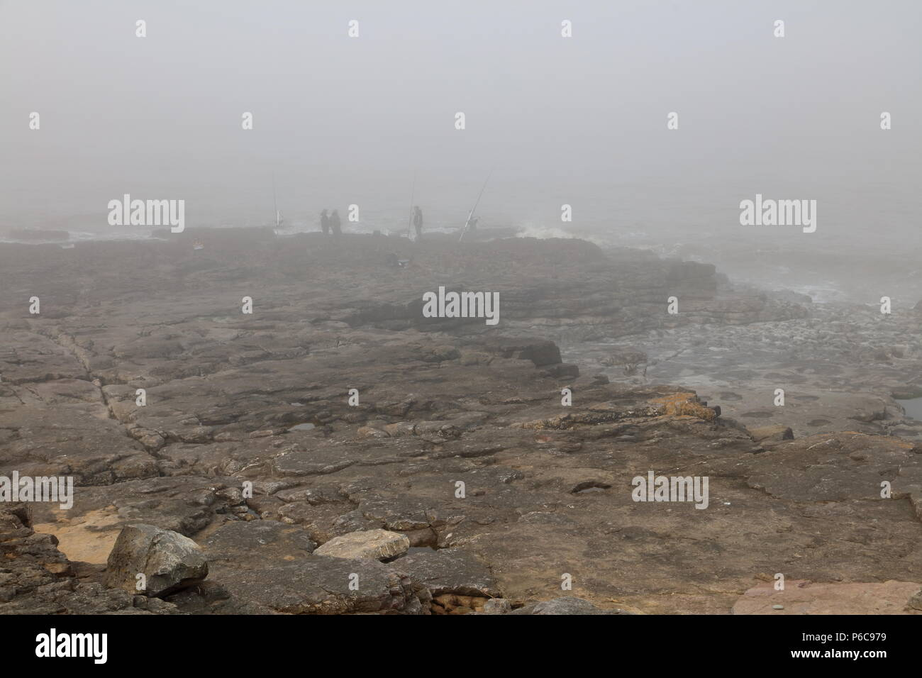 A group of fishermen in the distance on a very misty day with dense sea fog rolling in from the sea on the rocks at Ogmore by sea.. - Stock Image