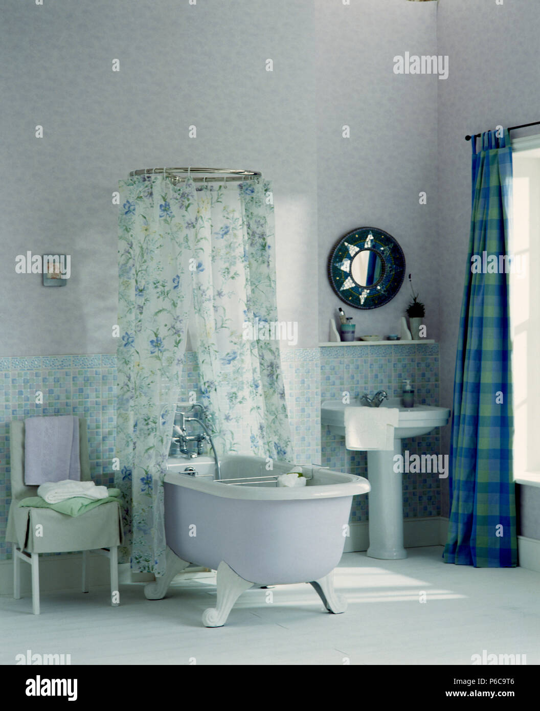 White rolltop bath with floral shower curtain in centre of white ...