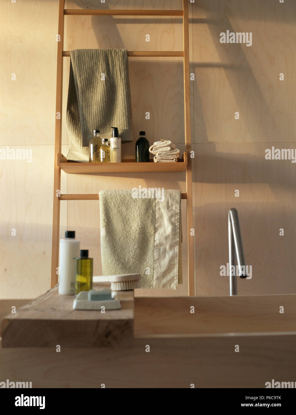 Bottles of toiletries and towels on simple wood and bath rack Stock ...