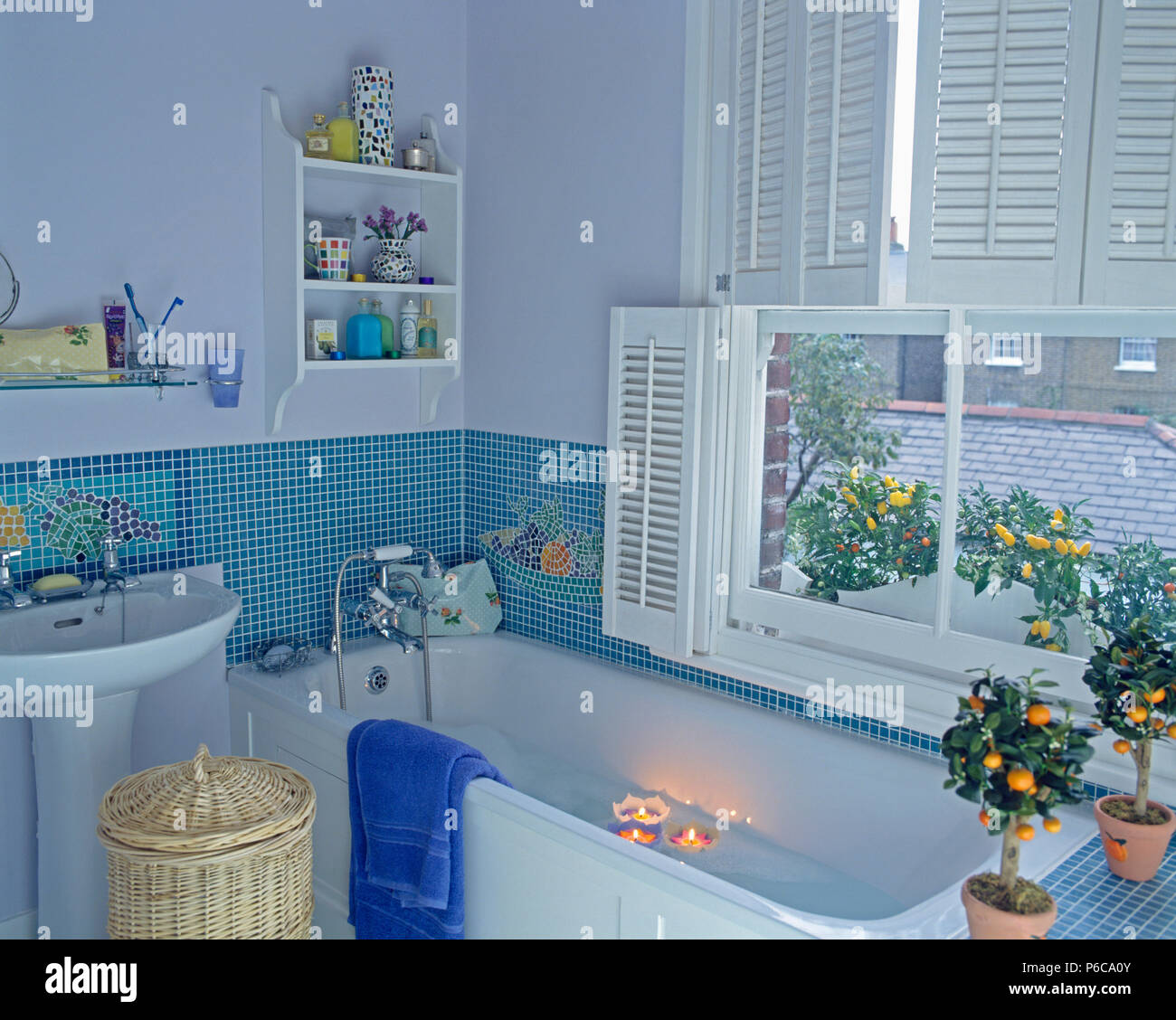 Candles floating in bath below window with white plantation shutters ...