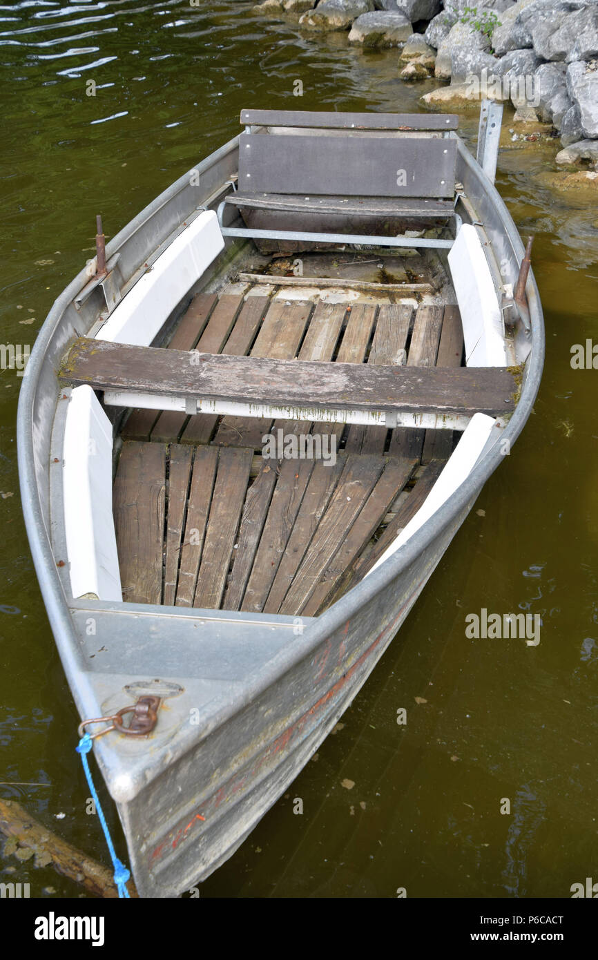 old rowing fishing and bathing boats in a lake in bavaria, neglected old and rotten row boat made of metal and wood Stock Photo
