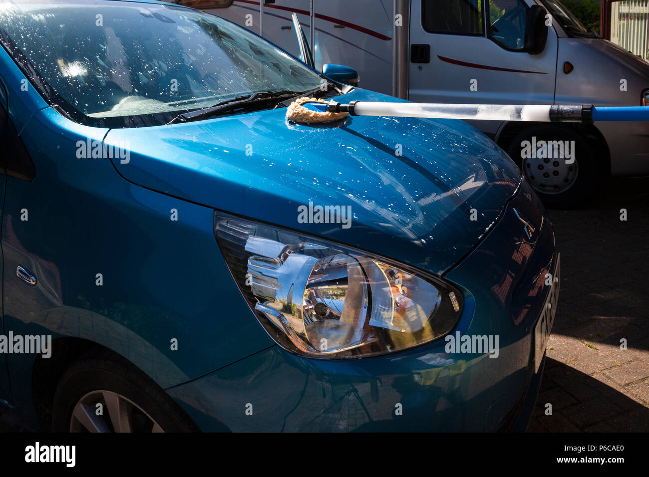 Washing car using collected rainwater during drought saving cost of metered water - Stock Image