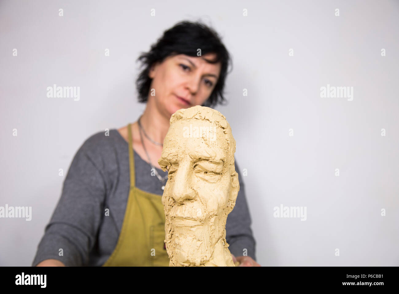 Sculptor artist creating a bust sculpture with clay. She is happy of her work, she is concentrated, she is sculpting a woman. - Stock Image