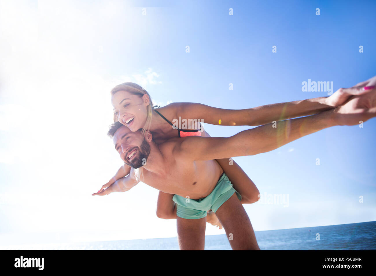 Handsome man giving piggy back to his girlfriend. - Stock Image