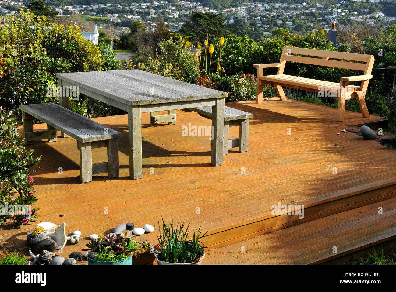 Macrocarpa (Monterey cypress) outdoor furniture on timber deck. Table and benches are four years old; seat with back is new.. Stock Photo
