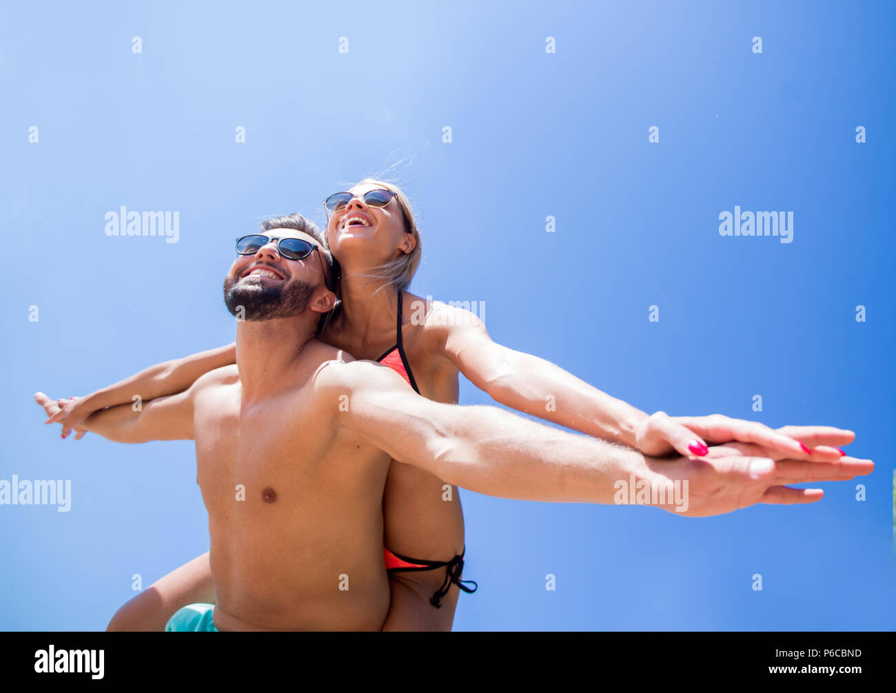 Man carrying woman piggyback on beach. - Stock Image