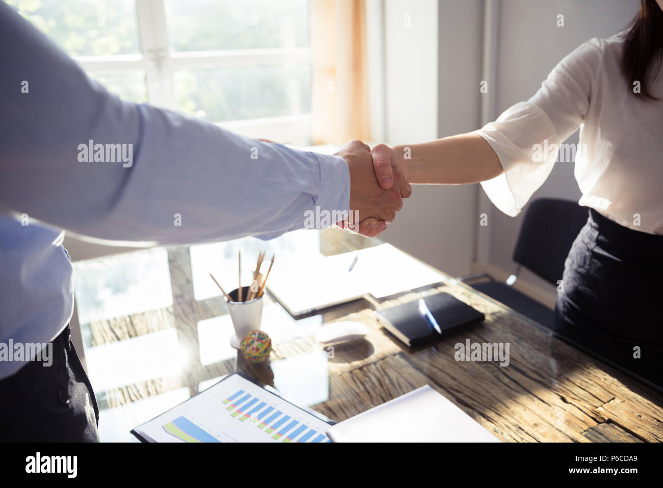 Close-up Of Two Business Partners Shaking Hands Over Desk In Office - Stock Image