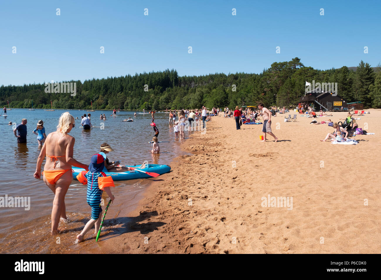 People sunbathing on beach during very hot weather in June 2018 at Loch Morlich near Aviemore in Highland region, Scotland UK - Stock Image