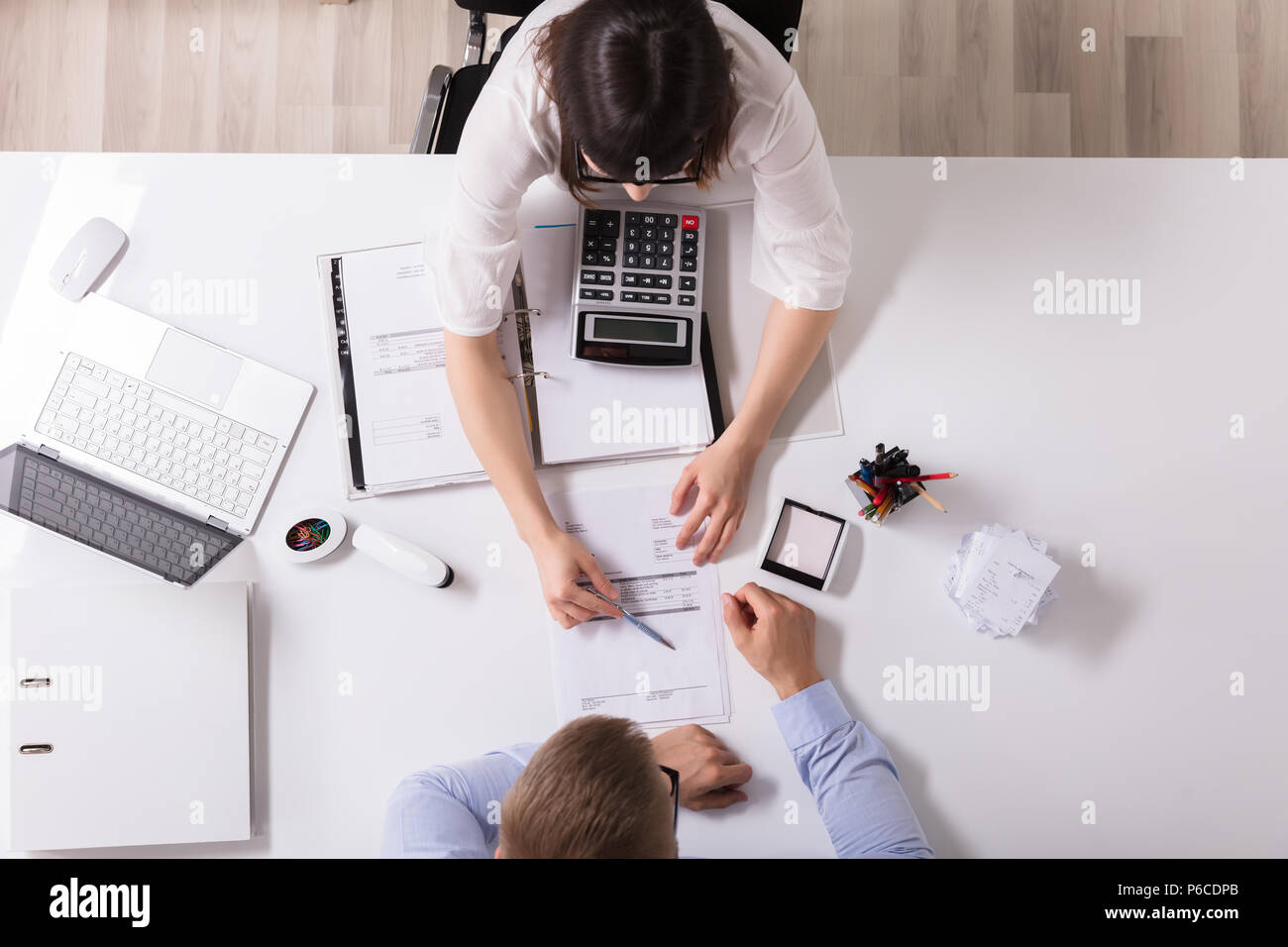 High Angle View Of Two Businesspeople Analyzing Bill In Office Stock Photo