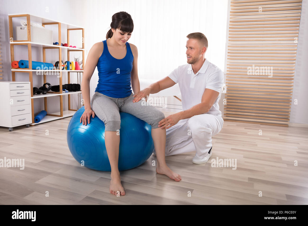 Male Physiotherapist Examining Smiling Young Woman's Injured Leg While Sitting On Fitness Ball - Stock Image