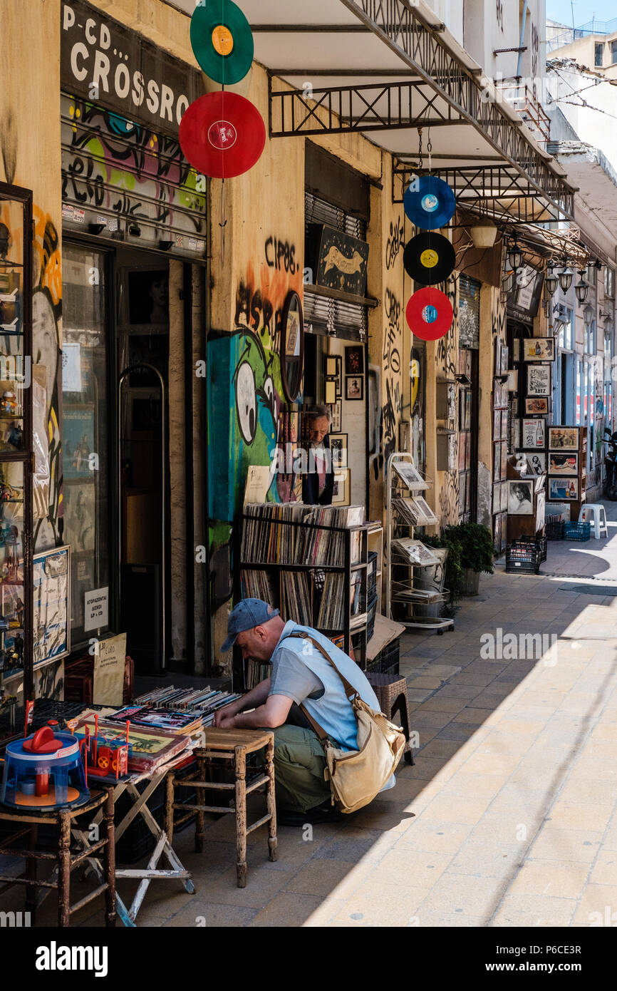Man searching through second-hand records in the Streets of Athens, Greece. - Stock Image