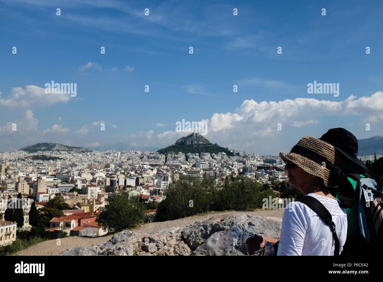 Couple on the Acropolis, enjoying the views of Athens and Mount Lycabettus ( Lycabettos ), and the blue skies, Athens, Greece. Stock Photo