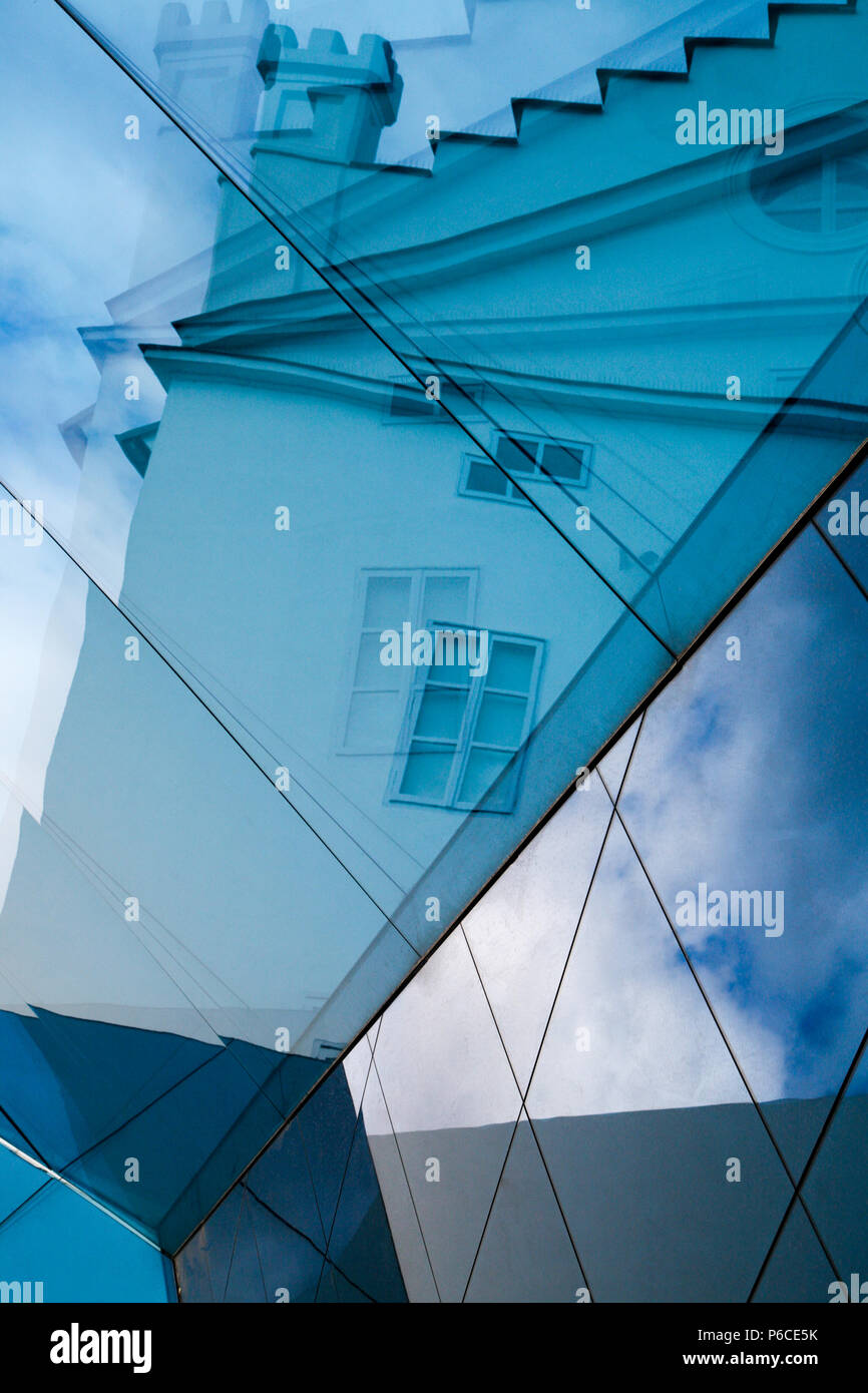 Blue abstract reflection of a traditional Prague turreted building taken from the glass roof of a modern art gallery Czech Republic. Stock Photo