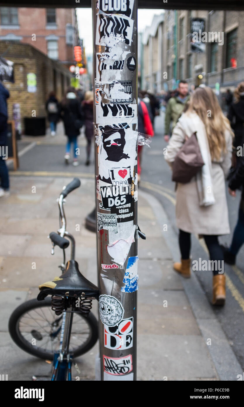 Street view of sign post in trendy Brick Lane decorated with a variety of artistic stickers and with a BMX leaning against it. London, England. Stock Photo