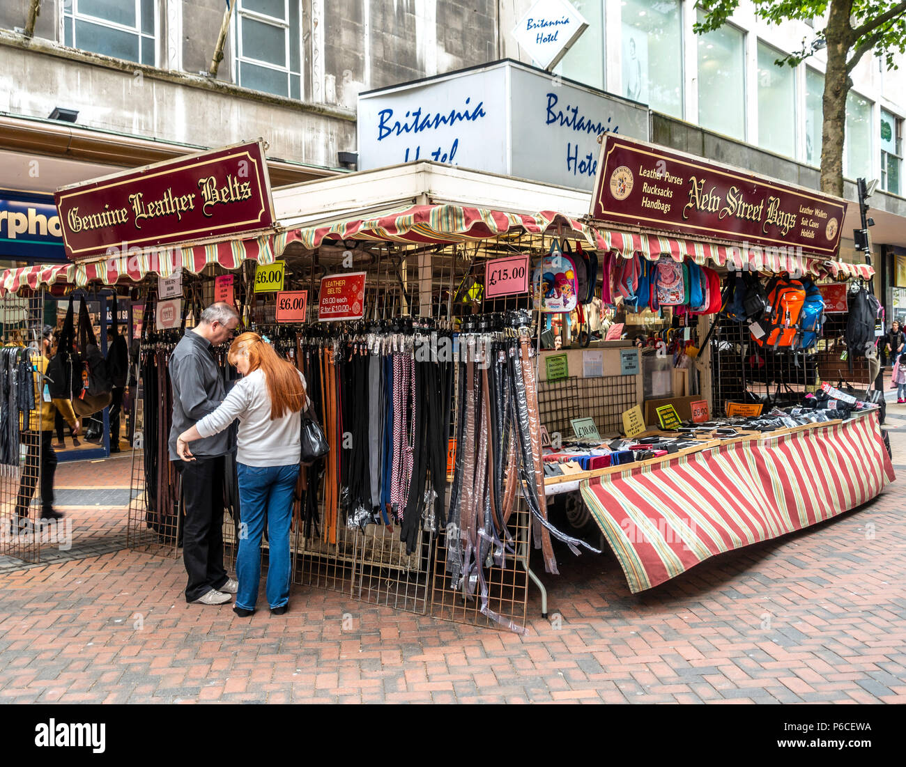 Customers examining leather belts at the New Street Bags trading stall in Mew Street, Birmingham City Centre, West Midlands, England, UK - Stock Image