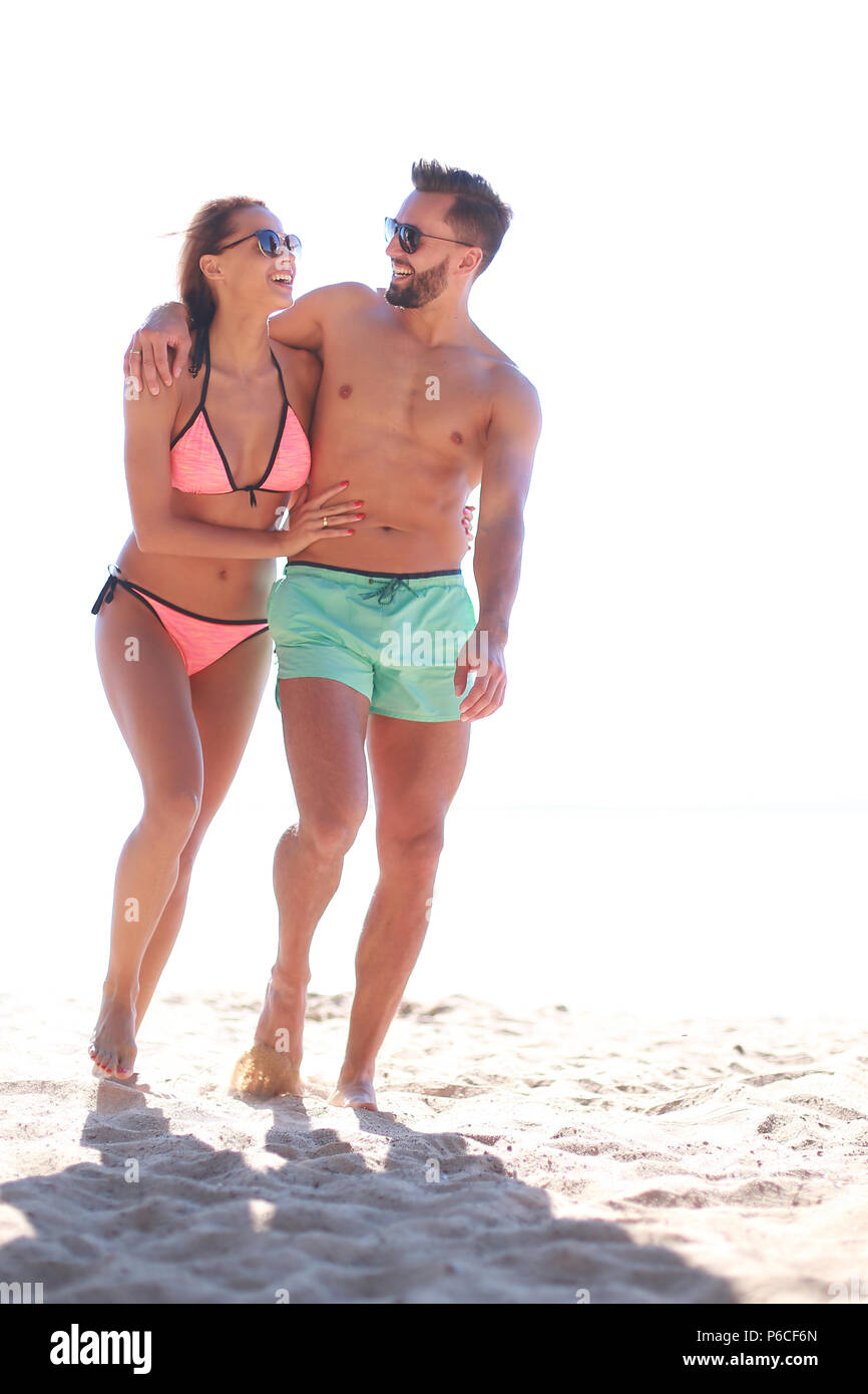 Young couple holding hands and walking on beach. - Stock Image