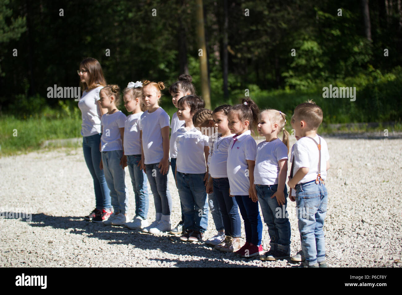 Little children in white t-shirts with painted faces lined up in line in summer day - Stock Image