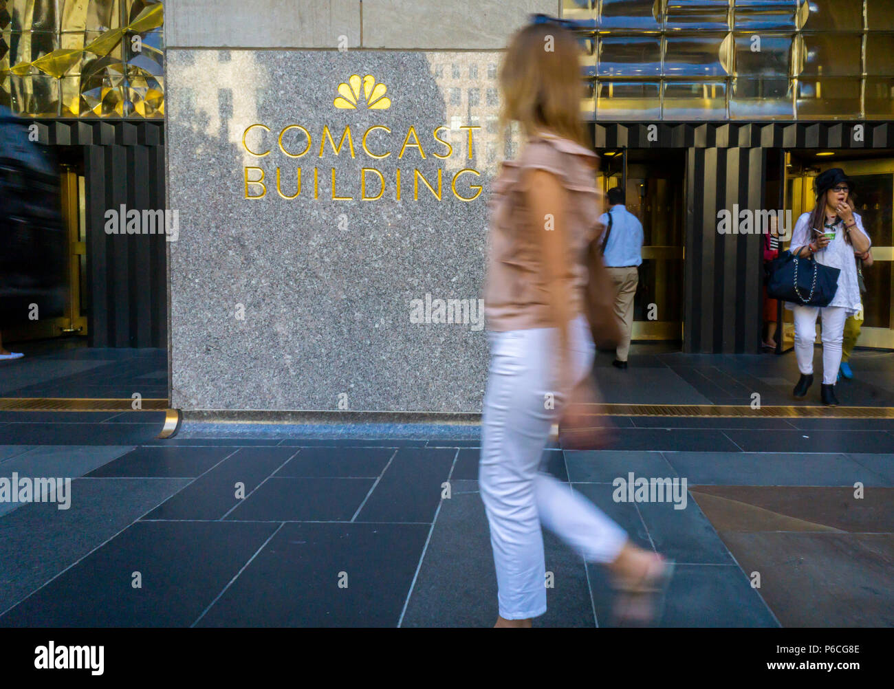 Tourists in Rockefeller Plaza in New York pass the Comcast building on Tuesday, June 19, 2018. Both Comcast and Disney are competing for the purchase of 21st Century Fox. (© Richard B. Levine) - Stock Image