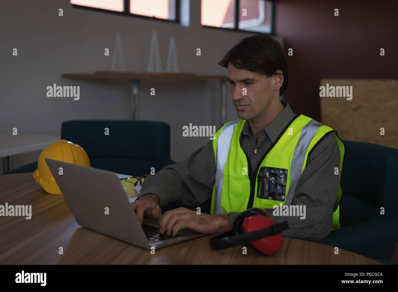 Male worker using laptop at desk - Stock Image
