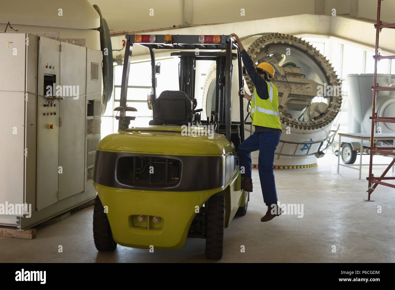 Male worker getting in forklift - Stock Image