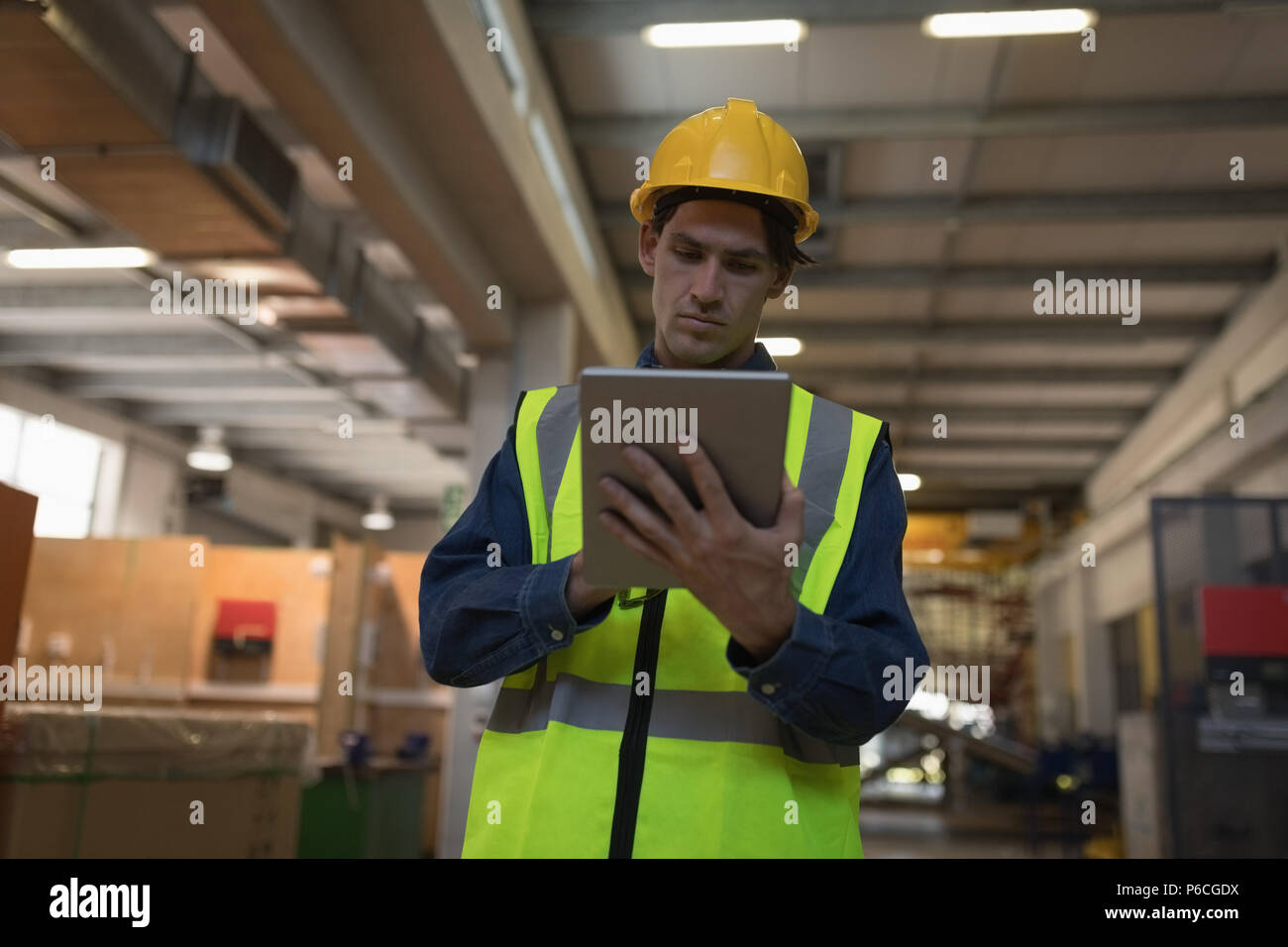 Male worker using digital tablet at solar station - Stock Image