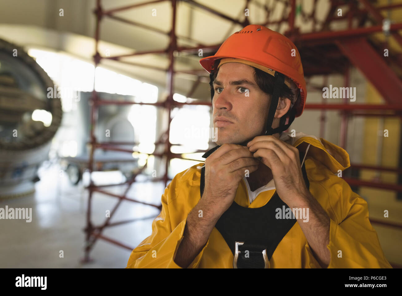 Male worker wearing hard hat at solar station - Stock Image