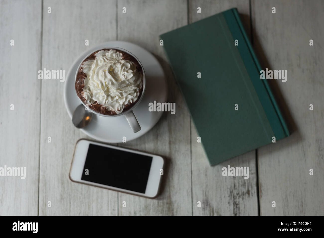 Sweet food, diary and mobile phone on wooden table Stock Photo