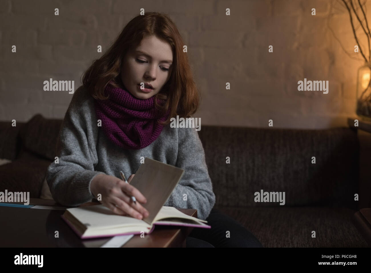 Woman writing note on diary in living room - Stock Image