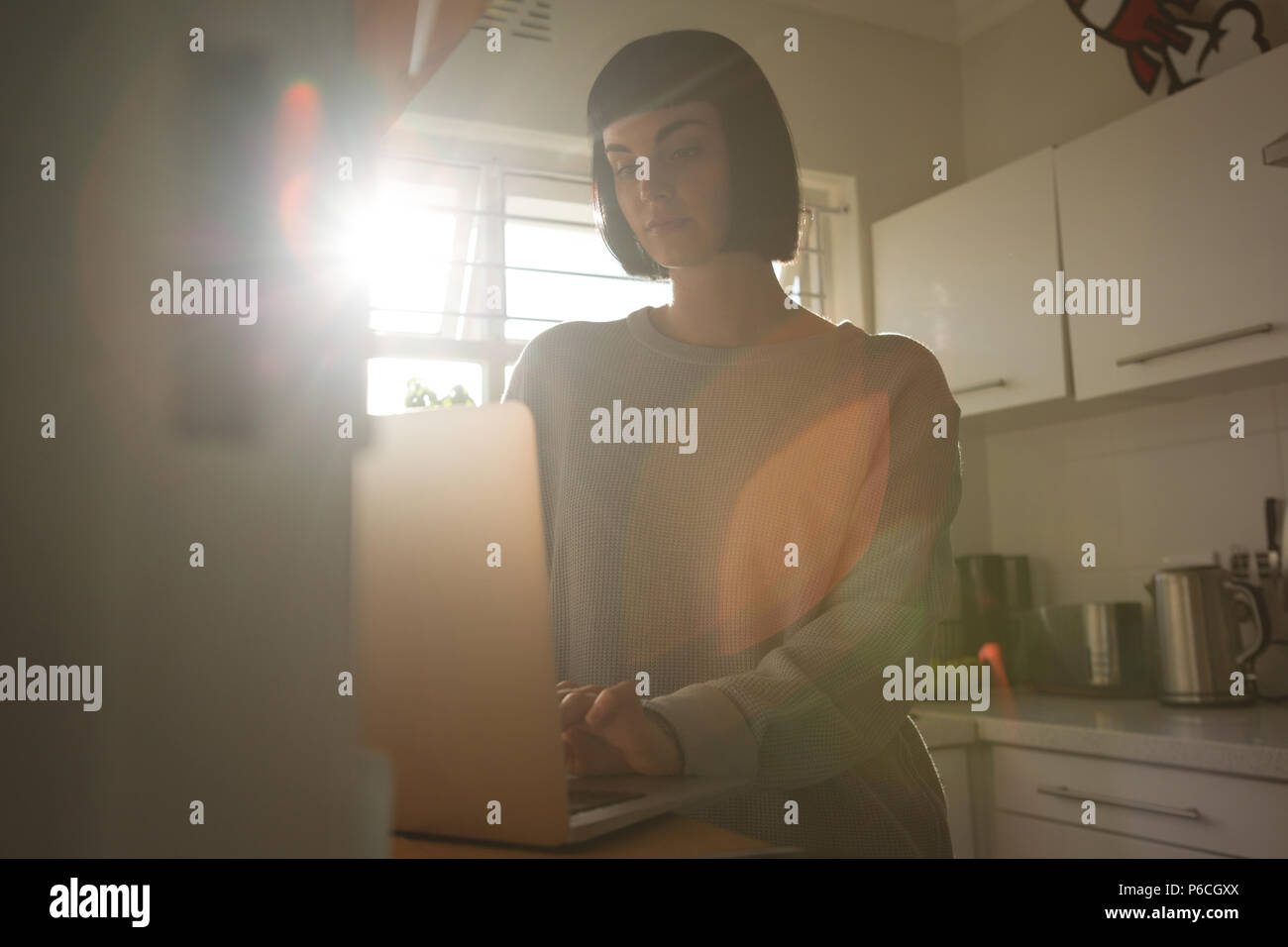 Woman using laptop in kitchen at home Stock Photo
