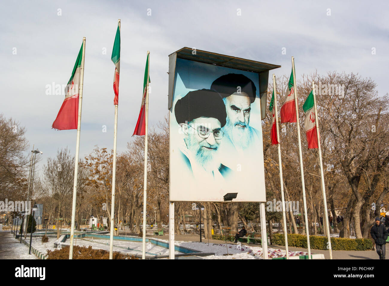 Images of Ali Khamenei, Supreme Leader of the Islamic Revolution and Ruhollah Khomeini on a billboard flanked my flag poles with the Iranian flag at t - Stock Image