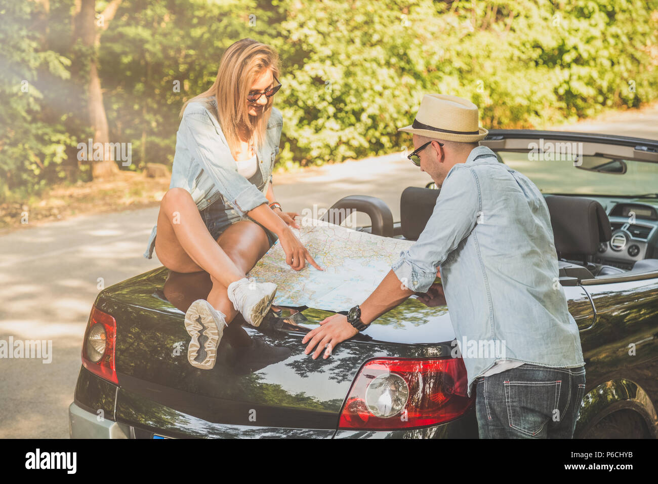 Beautiful couple looking at map on car trunk. Summer vacation road trip concept. - Stock Image