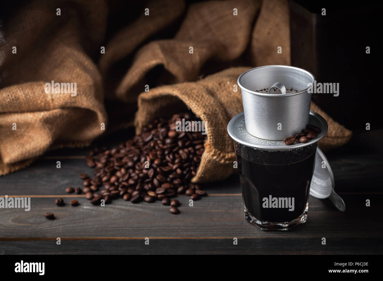 Vintage vietnam coffee dripper, coffee cup and coffee beans with bag. dark food style - Stock Image