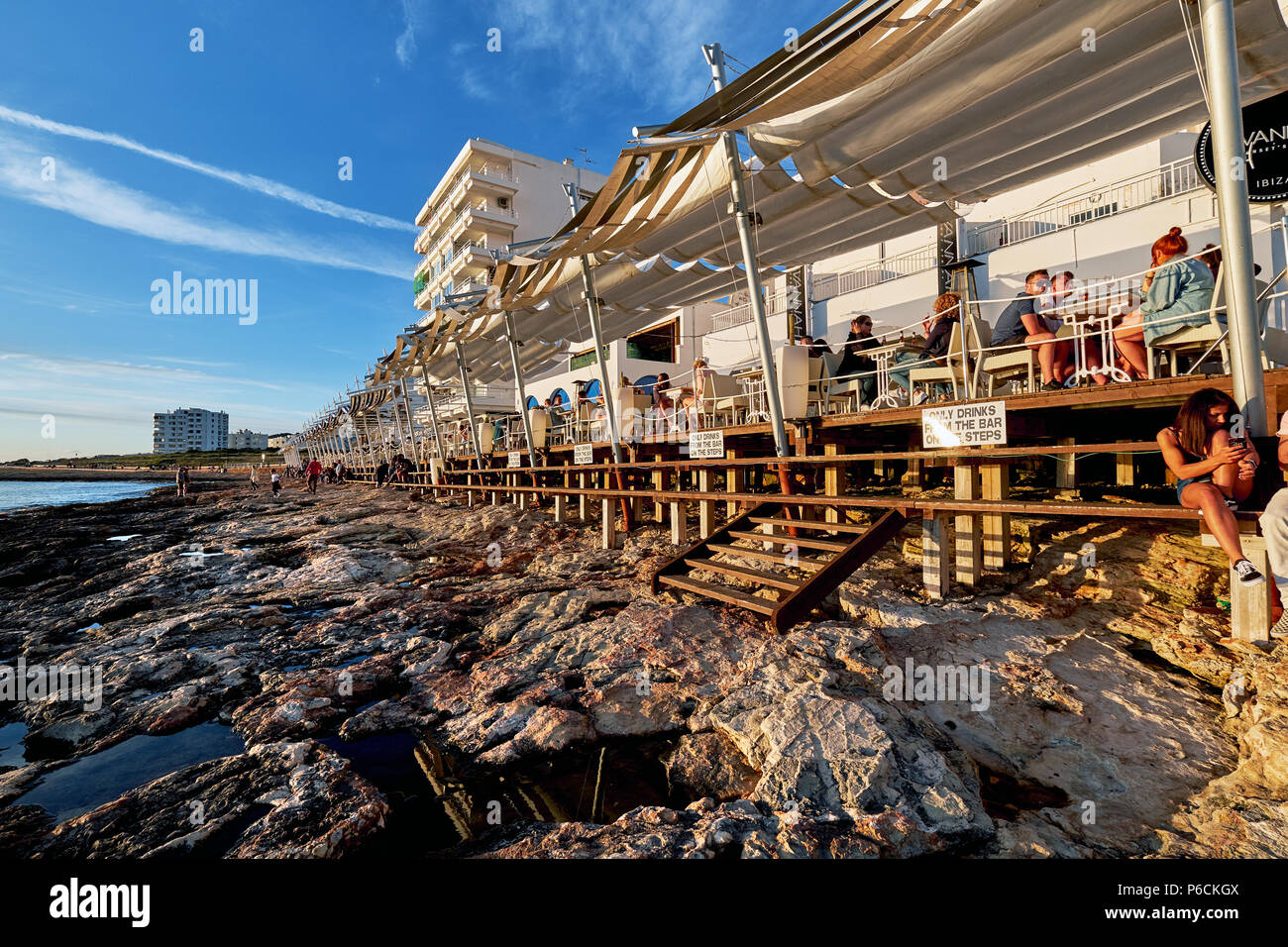 Ibiza Island, Spain - May 1, 2018: Crowds of people meet the sunset at the seafront terrace of Cafe Del Mar. This place is famous for views to the sun - Stock Image