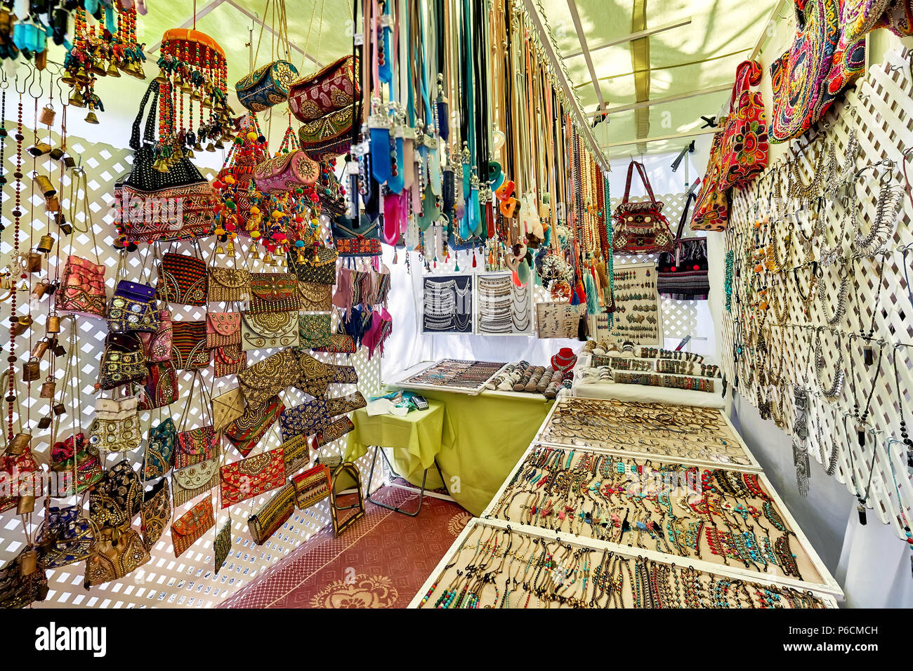 Ibiza Island, Spain - May 2, 2018: Stall full of a handmade fashion accessories, silver jewellery with precious gems and bohemian style of bags in the Stock Photo