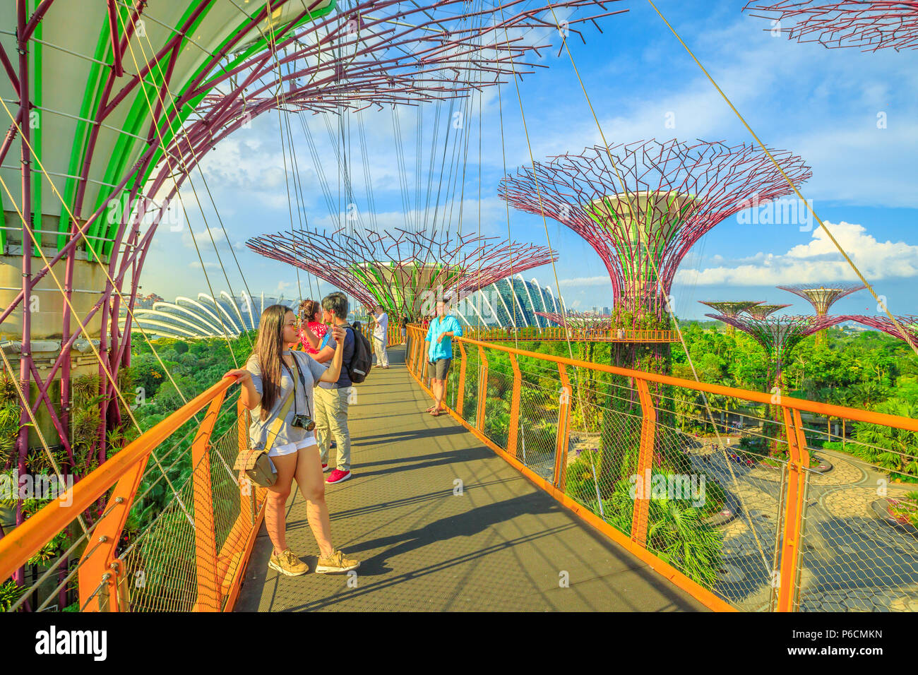 Singapore - April 29, 2018: asian tourist takes selfie with smart phone while walking on skybridge or OCBC Skyway of Supertree Grove in Gardens by the Bay, Marina Bay in Singapore. Stock Photo