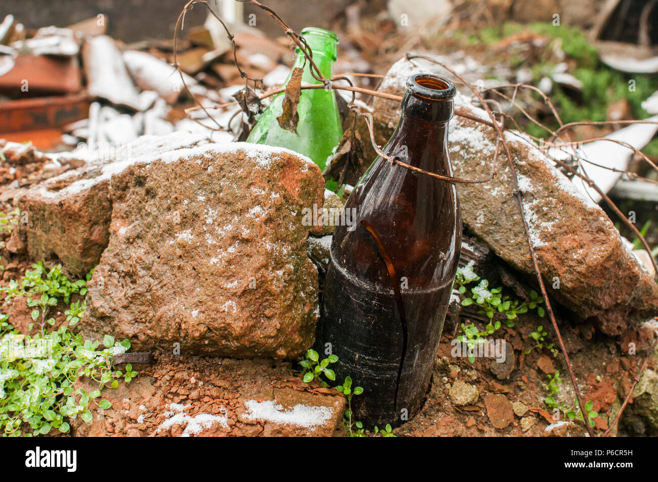 Broken grunge dirty beer bottles abandoned in ruins of demolished house closeup - Stock Image