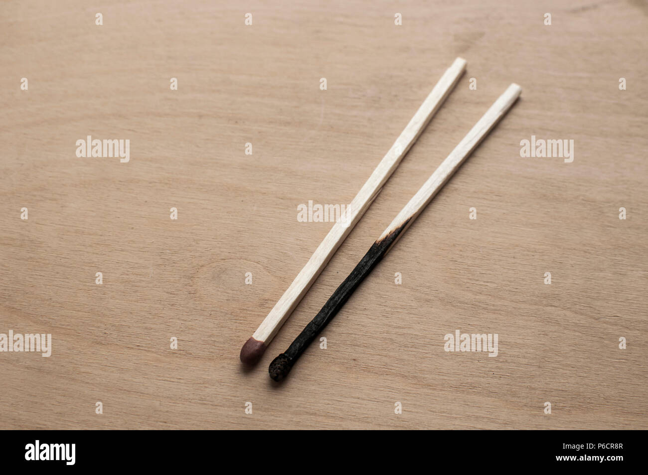 Burnt and whole head long wooden safety matchsticks on wooden background - Stock Image