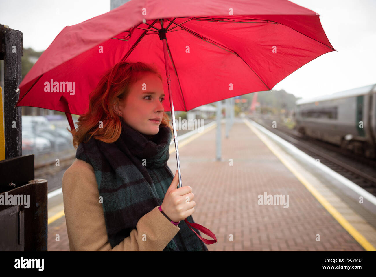 Young woman with umbrella waiting for train on platform - Stock Image