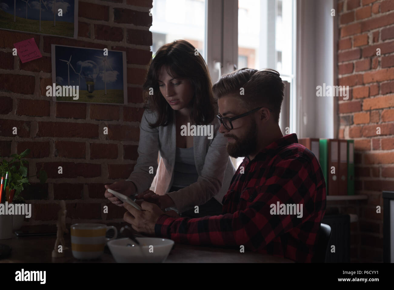 Male and female executives discussing over digital tablet - Stock Image