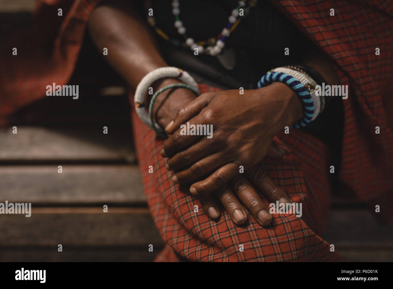 Maasai man in traditional clothing sitting on bench - Stock Image