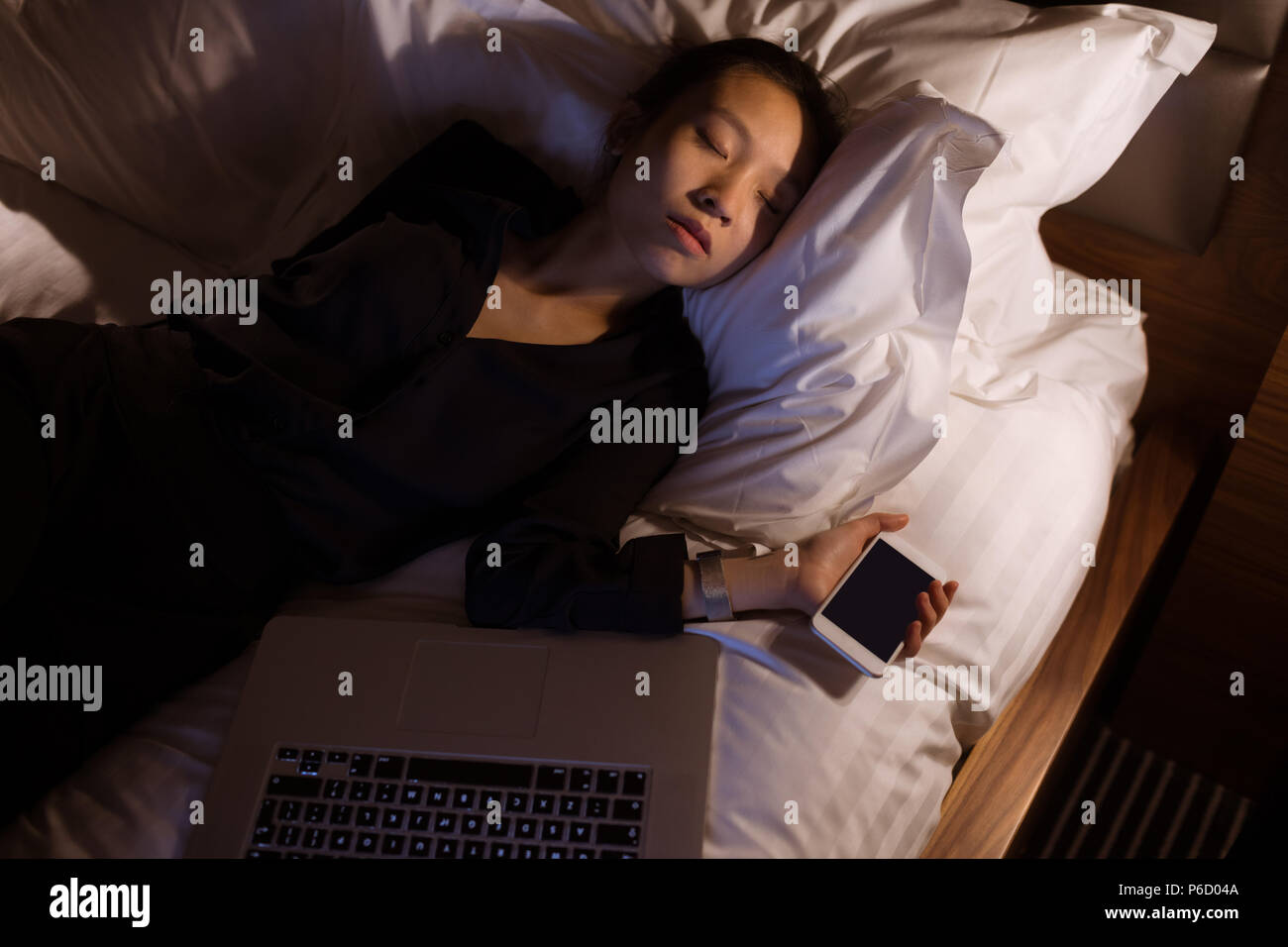 Tired woman sleeping with laptop and mobile pone on bed - Stock Image