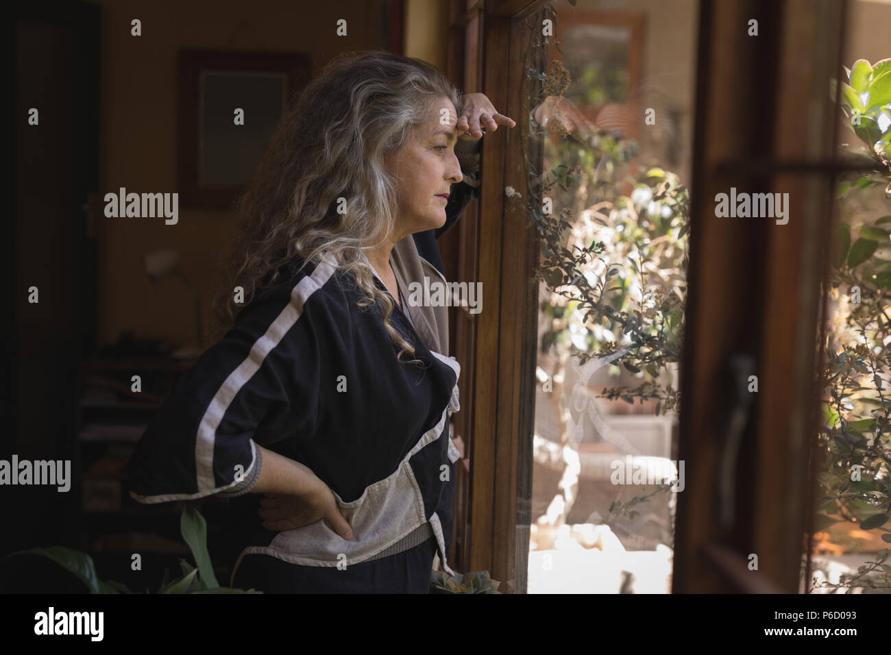 Thoughtful mature woman looking through window - Stock Image