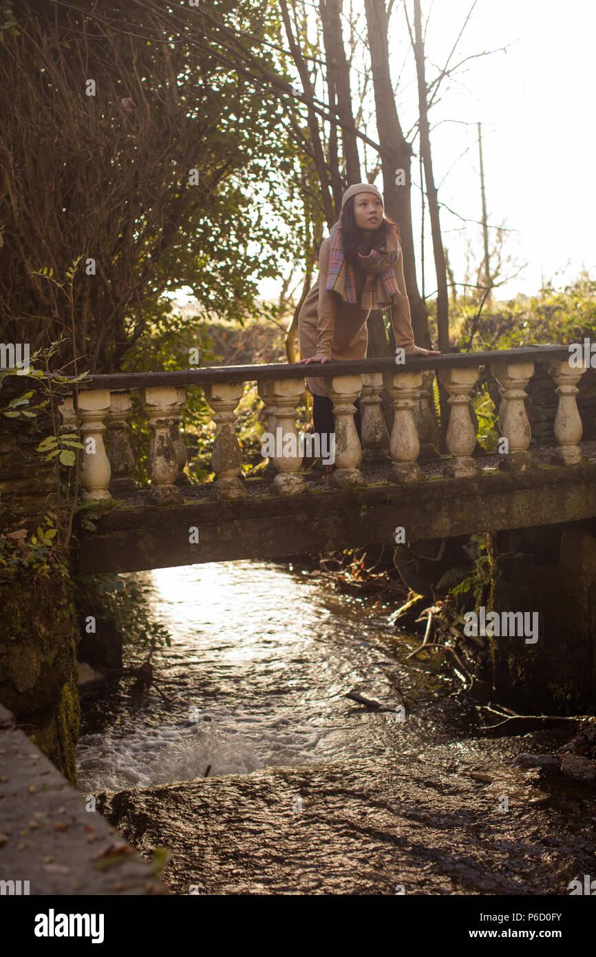 Thoughtful woman leaning on footbridge Stock Photo