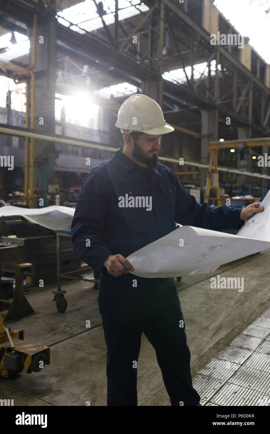 Technician looking at blue print - Stock Image
