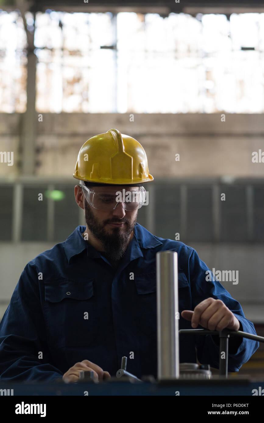 Technician in protective workwear cutting metal Stock Photo