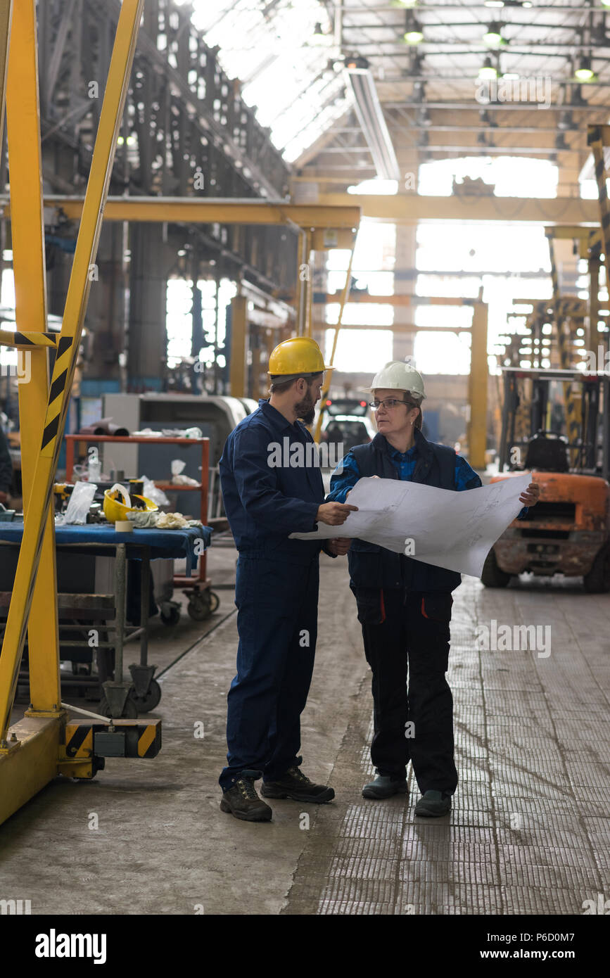 Technician discussing blueprint with his colleague - Stock Image