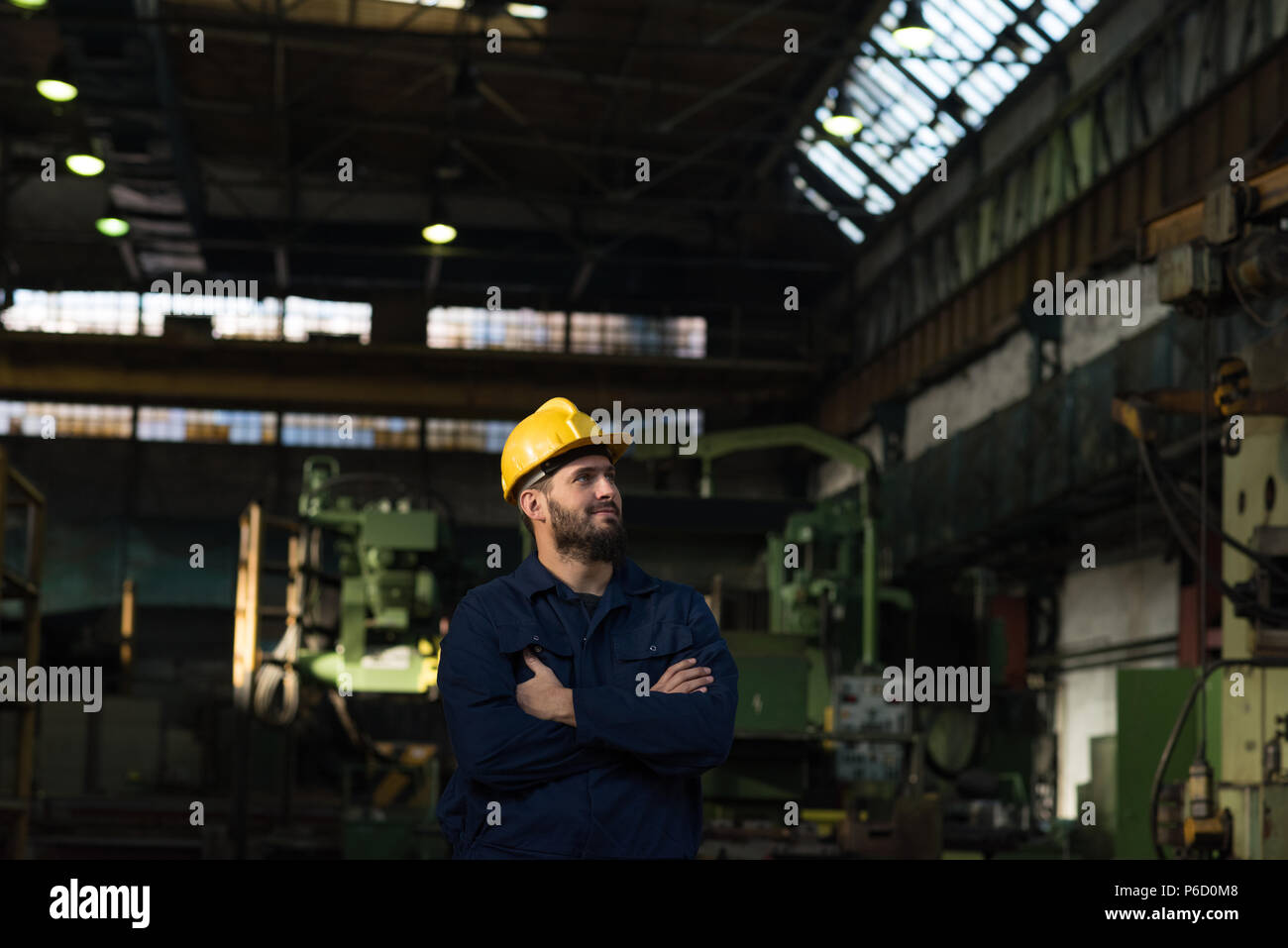 Thoughtful technician standing with arms crossed - Stock Image