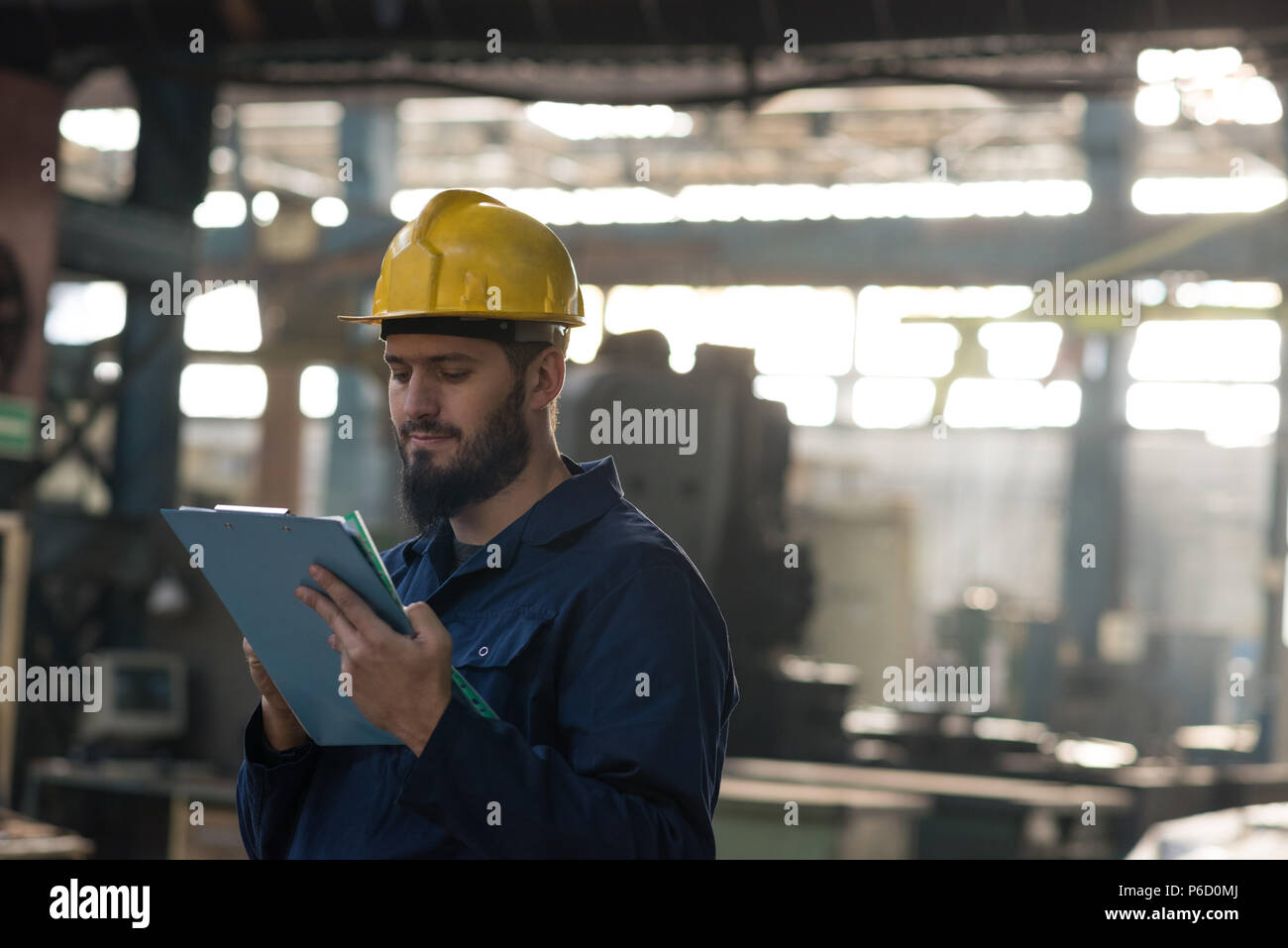 Technician maintaining record on clipboard - Stock Image