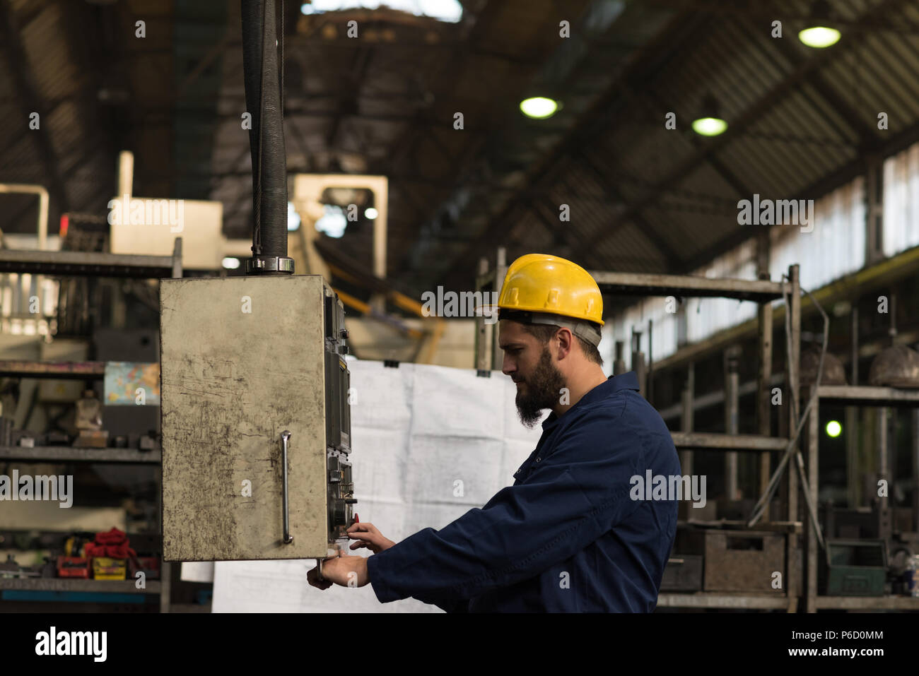 Technician checking machine in factory - Stock Image
