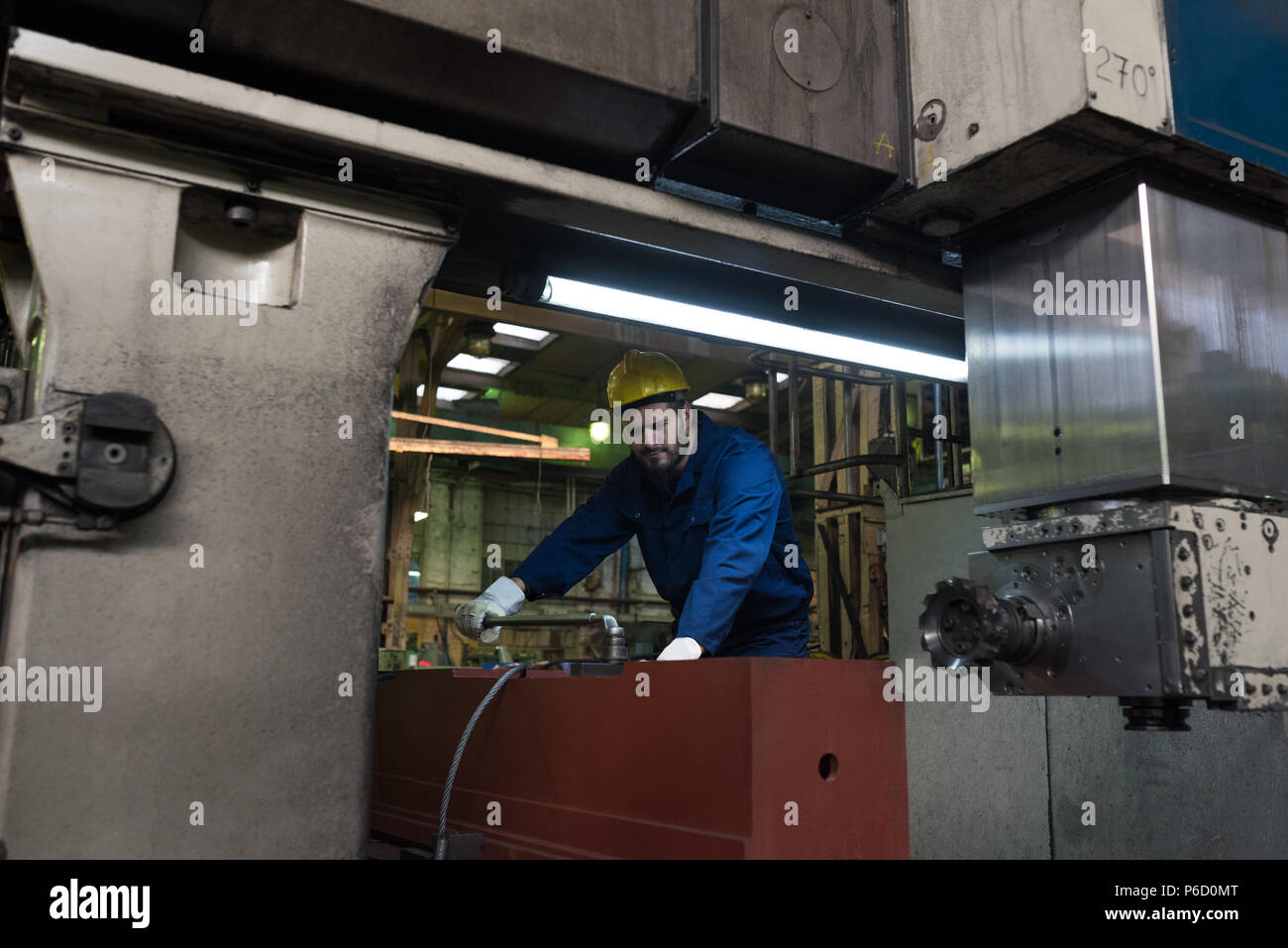 Technician in protective workwear cutting metal - Stock Image